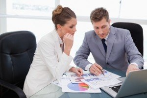 Business plan guide: researching your market & getting funding - image - Suited man and woman in a meeting discussing graphs
