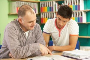 How to Get Top Marks With Your Start-Up Tutoring Business - image - male tutor teaching male student
