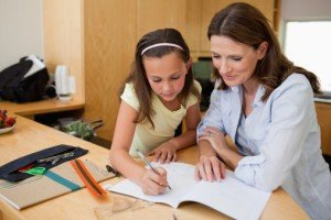 How to Get Top Marks With Your Start-Up Tutoring Business - image - female teacher with girl student at a desk