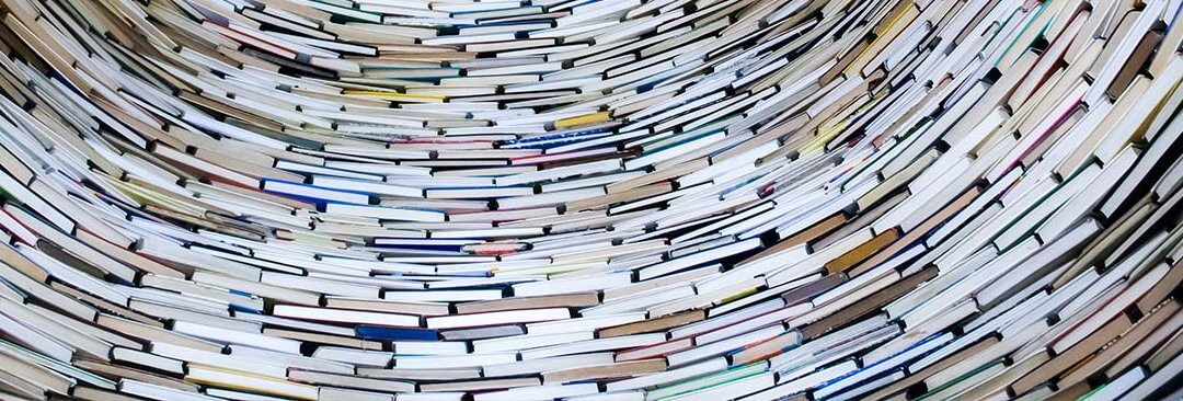 10 Best Books for Entrepreneurs image - a stack of multicolored books in a semicircle
