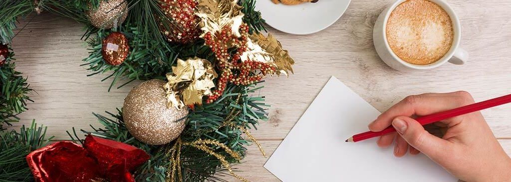 Christmas Marketing Ideas for Small Businesses 2017 - person making notes with pen and paper on a tabletop with Christmas wreath