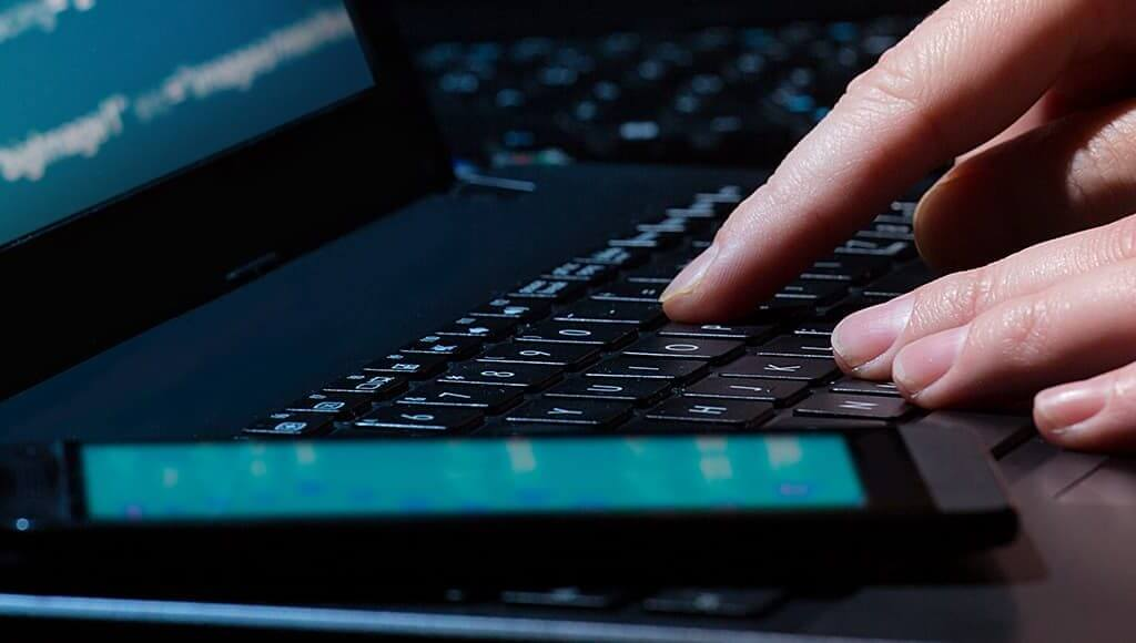 Spot The Red Flags: How To Protect Your Business From Cyberattacks image - hacker typing code into a black laptop