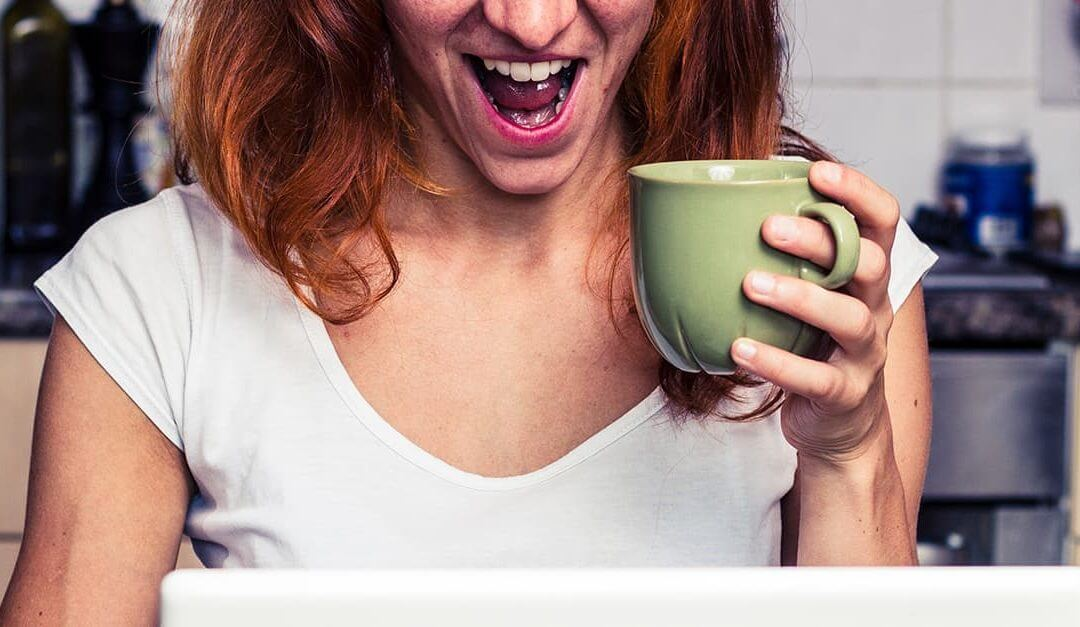 Ecstatic mumpreneur in the kitchen holding a coffee cup