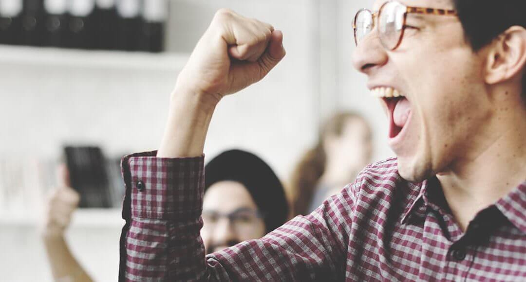 Startup Life Hacks image - bespectacled man in shirt fist pumps in an office