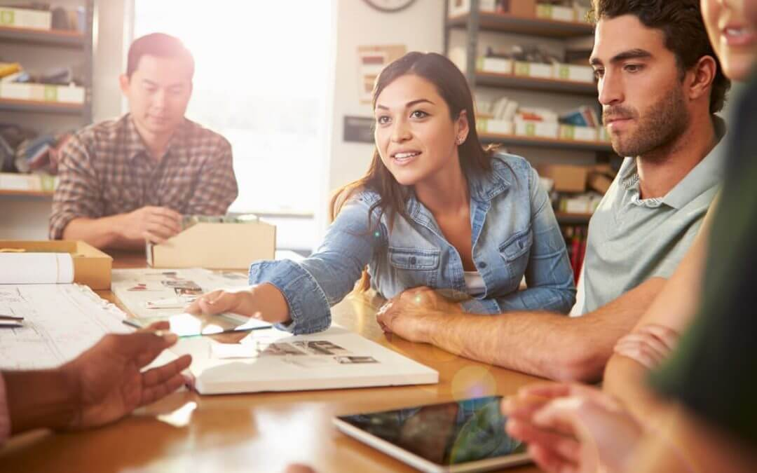 The Startup Working Environment – a Challenging Space or the Space to take on Challenges? image - woman with brown hair sat at a table discusses a creative project with three male colleagues