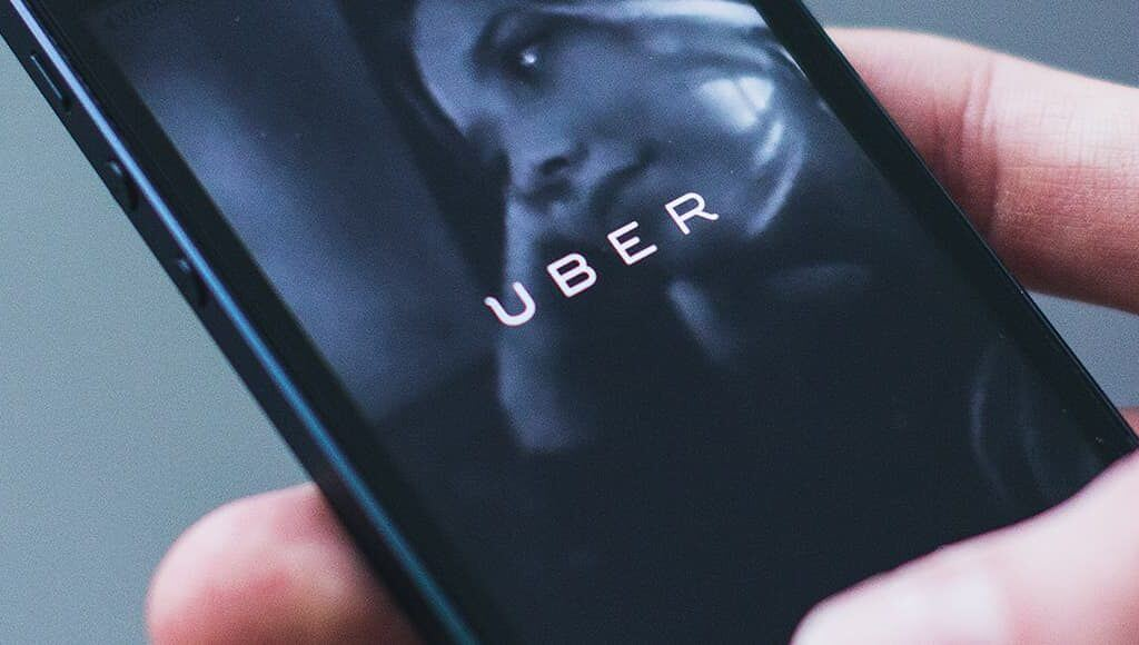 What Is the Uber Ruling and How Will It Affect Small Businesses? image - hand holding phone with uber app open