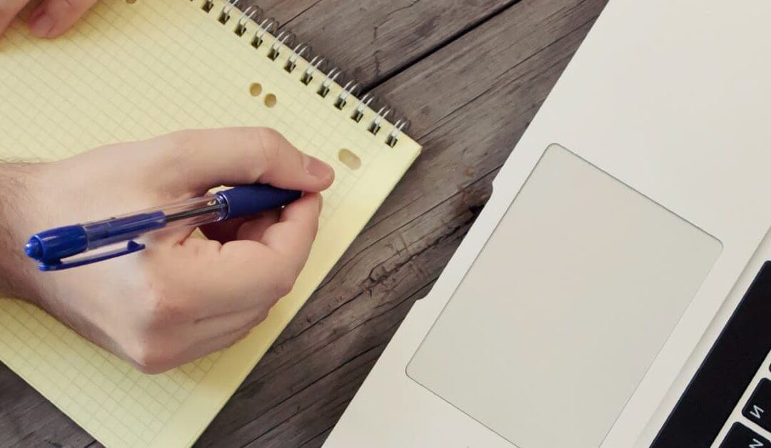 Business start up owner writing blog ideas into a notepad