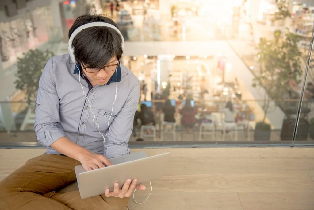 Image - young man sitting on floor in a co-working space using laptop and headphones